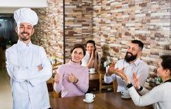 Le chef heureux écoute l'éloge de la nourriture Photo stock