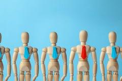 Le chef mène l'équipe d'affaires au bon bon but Chef dans le lien rouge et équipe dans les liens bleus photo libre de droits