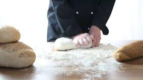 Le chef malaxent la pâte sur une table en bois banque de vidéos