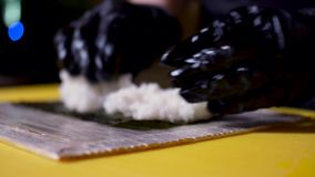 Le chef mettant le riz sur la feuille de nori, concept japonais de cuisine Vue Fermez-vous pour des mains dans les gants ? cuire  banque de vidéos