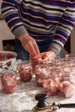 Le chef prépare la conservation de pré-maison Un homme met des morceaux de viande crue dans des pots en verre photographie stock libre de droits