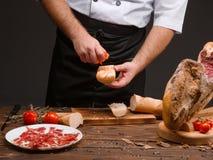 Le chef prépare le pain de tomate avec du jambon Délicatesse d'Espagnol de Jamon Images stock