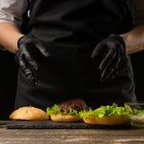 Le chef prépare un hamburger, un hamburger Sur un fond avec des ingrédients Aliments de préparation rapide délicieux et, aliments photos stock