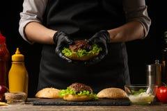 Le chef prépare un hamburger, un hamburger Sur un fond avec des ingrédients photo libre de droits