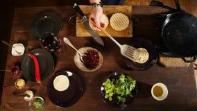 Le chef prépare une côtelette pour un hamburger avec du fromage Longueur courante Vue supérieure sur les préparations de processu clips vidéos