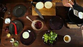 Le chef prépare une côtelette pour un hamburger avec du fromage Longueur courante Vue supérieure sur les préparations de processu banque de vidéos