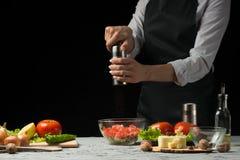 Le chef prépare une salade, avec un moulin de poivre sur un fond foncé avec un espace vide pour l'inscription photo stock