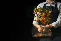 Le chef prépare une salade, avec un moulin de poivre sur un fond foncé avec un espace vide pour l'inscription photographie stock libre de droits