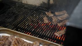 Le chef prend les biftecks de finition du gril Gril argentin de flammes et de braises rouges Préparation du feu et de gril pour clips vidéos