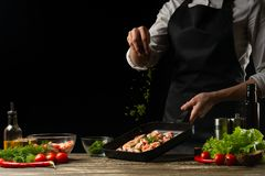 Le chef professionnel arrose des crevettes pour la salade, des fruits de mer et le concept sain de nourriture Photo horizontale,  image stock