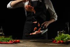 Le chef professionnel prépare une salade de crevette fraîche, et de légumes sur un fond foncé, gelant dans le mouvement Fruits de photo libre de droits