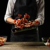 Le chef professionnel prépare une salade de crevette fraîche, et de légumes sur un fond foncé, gelant dans le mouvement Fruits de image stock