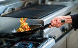 Le chef rôtit des légumes dans la casserole Photographie stock