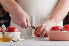 Le chef remet enlever le puits de la pomme fraîchement épluchée utilisant un k de épluchage photo stock