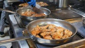 Le chef retourne la viande de deux scapulars qui est faite frire dans des deux poêles dans la cuisine du restaurant, la viande clips vidéos