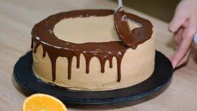 Le chef serre la crème Cerise sur le gâteau de chocolat Gâteau blanc couvert du chocolat et de crème Décoration de gâteau de choc banque de vidéos