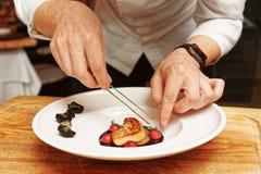 Le chef sert des gras de foie, modifiés la tonalité photographie stock