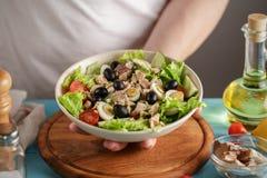 Le chef sert la cuvette avec de la salade de thon, des tomates-cerises et des olives photographie stock