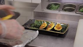 Le chef servant le plat japonais traditionnel a servi du plat en pierre noir banque de vidéos