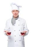 Le chef tient deux verres de vin rouge sur un blanc Image stock