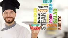 Le chef tient un plat avec différents noms de nourriture et de repas banque de vidéos