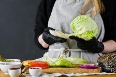 Le chef tire la laitue Le concept de faire cuire un hamburger noir Recette faite maison d'hamburger Cuisine, vue de c?t?, l'espac photo stock