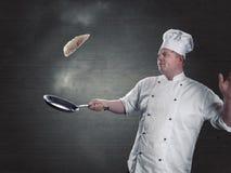 le chef tourne les crêpes fraîches dans la casserole Photo stock