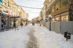Le chemin étroit parmi la neige dérive dans la rue principale du Bulgare Pomorie d'hiver Images libres de droits
