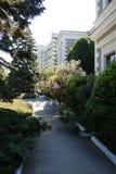 Le chemin autour du bâtiment passe par la floraison, buissons verts photographie stock libre de droits