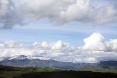 Le chemin avec la neige de l'Utah a couvert des montagnes avec rouler les collines vertes Photographie stock libre de droits