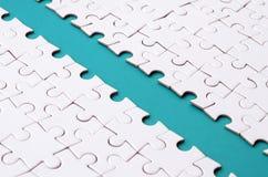 Le chemin bleu est étendu sur la plate-forme d'un puzzle denteux plié blanc Image de texture avec l'espace de copie pour le texte photographie stock libre de droits