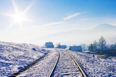 Le chemin de fer dans la neige a couvert des montagnes Photographie stock