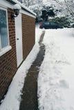 Le chemin de jardin a effacé par la neige de la maison au véhicule Image stock