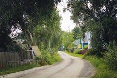 Le chemin de terre et les maisons Rue de village images libres de droits