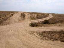 Le chemin de terre poussiéreux mène au dessus de la colline Image libre de droits