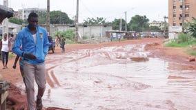 Le chemin de terre rouge avec de l'eau dans quelques endroits mène à un village clips vidéos