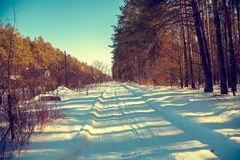 Le chemin de terre s'est recroquevillé avec la neige Horizontal rural de l'hiver photo stock