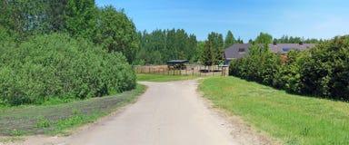 Le chemin de terre de village mène à la ferme de cheval Image stock