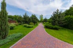 Le chemin en parc est présenté avec les tuiles rouges entre les herbes vertes et les buissons ornementaux Mezhygirya Ukraine image stock