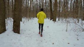 Le cheminement du tir de l'homme sportif fonctionnant dans la forêt sur la neige a couvert le chemin le jour d'hiver banque de vidéos