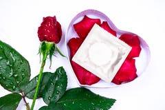 Le cher amour, les roses, occasions spéciales, avec des préservatifs, a isolé le fond Photos stock