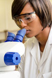 Le chercheur féminin africain regarde dans le microscope photo stock