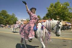 Le cheval et le cavalier décorés joyeux font leur rue principale de manière vers le bas pendant un quatrième de défilé de juillet Photo stock