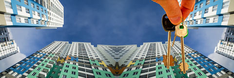 Le chiavi all'appartamento sui precedenti di cielo blu e delle nuvole Immagini Stock Libere da Diritti