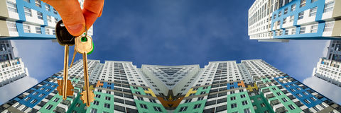 Le chiavi all'appartamento sui precedenti di cielo blu e delle nuvole Fotografia Stock