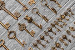 Le chiavi antiche d'annata si trovano diagonalmente su un fondo di legno grigio chiaro Fotografia Stock