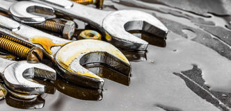 Le chiavi, dadi - e - bulloni hanno macchiato con l'olio di motore Fotografia Stock Libera da Diritti