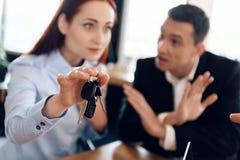 Le chiavi dell'automobile appendono sul dito della mano della donna che è in defocus Divisione della proprietà immagini stock libere da diritti