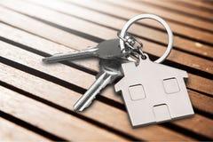 Le chiavi della Camera con la casa dipendono il fondo Immagine Stock