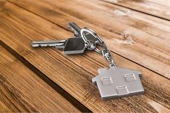 Le chiavi della Camera con la casa dipendono il fondo di legno Immagine Stock